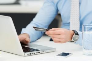 Mann mit Laptop und Kreditkarte